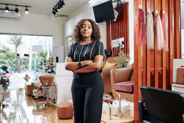 Confident attractive young Black woman standing in her beauty salon with arms folded and looking at camera