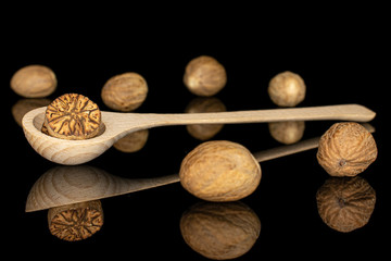 Fototapeta Group of six whole one half of dry brown nutmeg in a wooden spoon isolated on black glass obraz