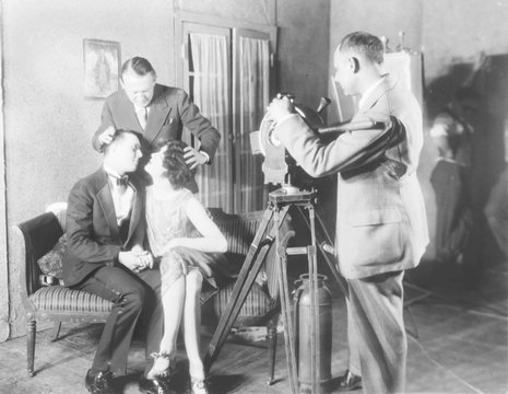 MGM director Edmund Goulding (back left), helping William Twiddy (left), and Bill Easton, kiss on set, while making a film with the motion picture class at Columbia University, New York, 1927