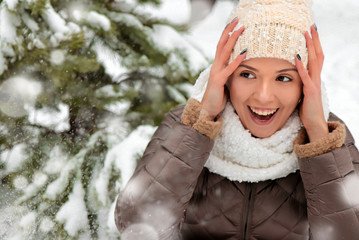 A young beautiful girl rejoices in the winter snow in the park among firs in a hat and scarf close-up.