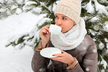 A young beautiful girl in winter on a walk gets warm with a hot drink on a walk in the Park next to a fir tree.