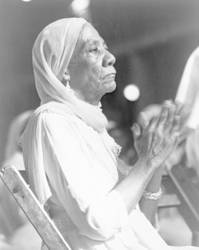 Elderly African American woman at a Black Muslim rally clapping her hands, New York City