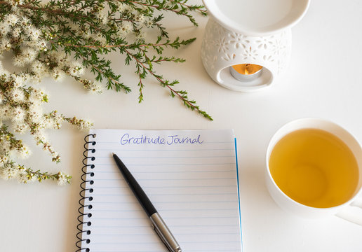 Close up of notebook and pen with handwritten Gratitude Journal text on table with oil burner and flowers (selective focus)