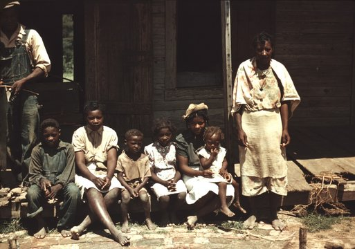 A rural African American family seated on the porch of their house on a house Bayou Bourbeau plantation, Natchitoches, Louisiana