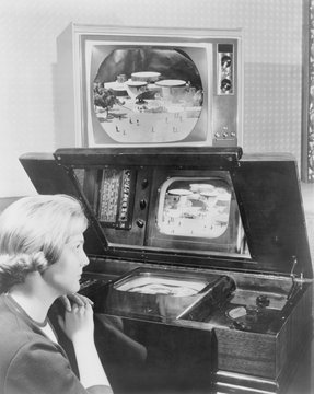 Woman looking at two television sets.One, similar to a set demonstrated at the 1939 New York World's fair, has a small screen incased horizontally in a large wooden cabinet and is viewed from a reflective mirror. The other, now displayed 25 years later