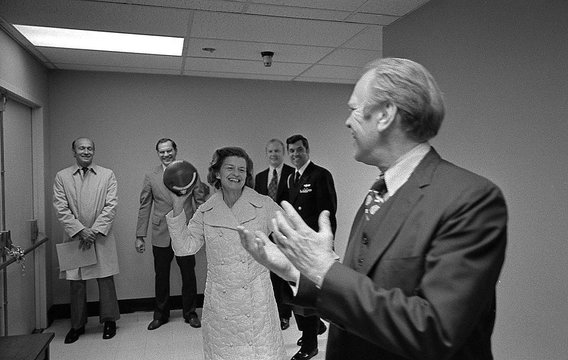 As she recovered from breast cancer surgery, President and Mrs. Ford toss a football, a gift from Washington Redskins Coach George Allen, in the hallway of Bethesda Naval Hospital