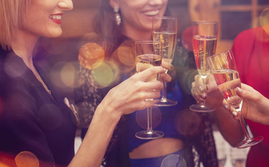 Woman's celebrating and toasting with champagne. Hands with a full glasses of sparkling wine
