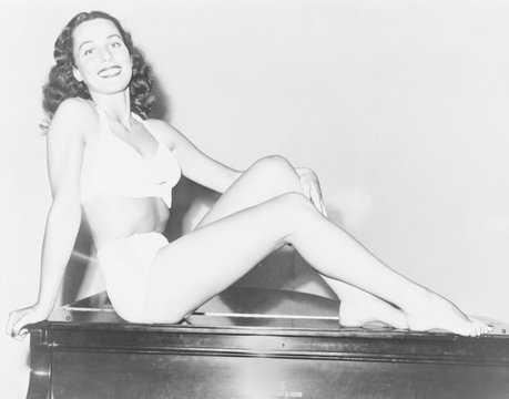 Bess Myerson (b. 1924), as Miss New York City seated on an upright piano in a two piece bathing suit