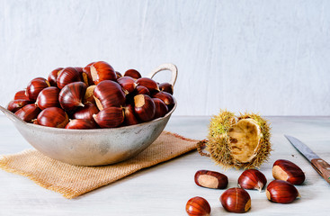 Chestnuts in a metallic basket on rustic wooden background