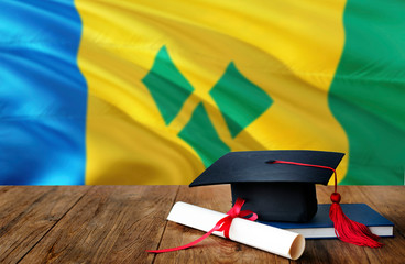 Saint Vincent And The Grenadines education concept. Graduation cap and diploma on wooden table,...
