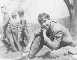 John Collier, Jr. (b. 1913), American photographer with the Farm Security Administration, seated on lawn with boys in the background