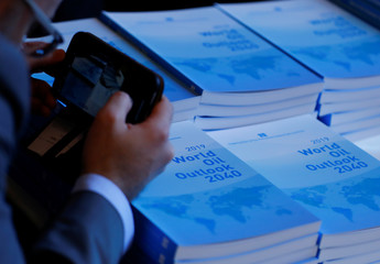 A man takes pictures of copies of the World Oil Outlook during its presentation in Vienna