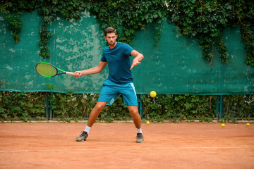 Fototapeta Skilled and agile tennis player having a practice at outdoor court. obraz