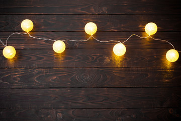 Christmas golden lights on dark wooden background