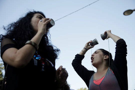 Demonstrators carry paper cup string phones as they protest outside the Touch telecommunications building in Beirut