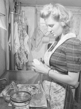 Young women peeling potatoes in her Washington D.C. apartment kitchen. She has a modern glass