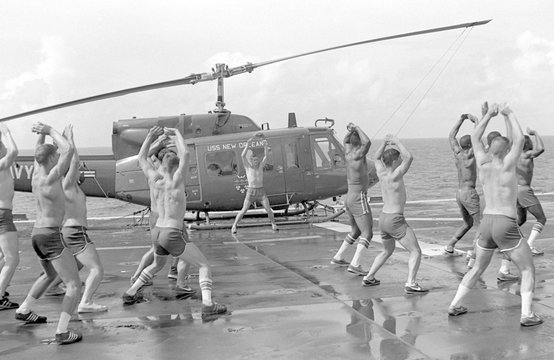 Marines doing jumping jacks on the deck of the amphibious assault ship USS New Orleans