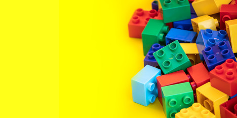 Colorful plastic building blocks toy bricks with place for you text and content.