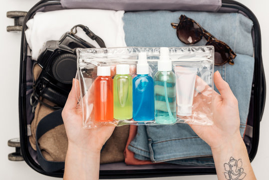 cropped view of woman packing travel bag with cosmetic bag with colorful bottles