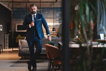 Stylish bearded man in a suit standing in modern office Wall mural