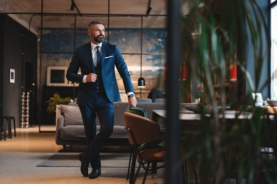 Stylish bearded man in a suit standing in modern office