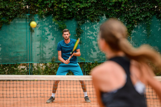 Couple playing tennis at outdoor court and have fun.