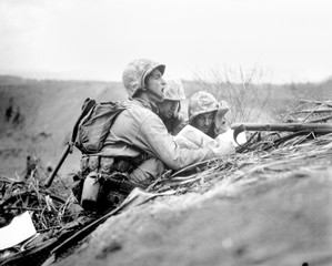 Marine observer finds the location of a machine gun nest on a map of Iwo Jima