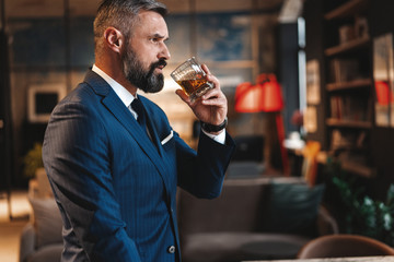 Mature handsome businessman stand and hold glass of whiskey in his own office.