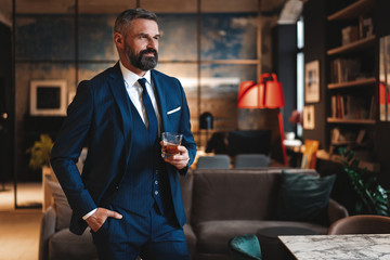Mature handsome businessman stand and hold glass of whiskey in his own office. Fototapete