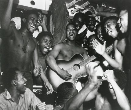 African American sailors aboard the U.S.S. Ticonderoga celebrate the news of Japan's surrender