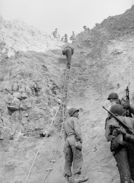 U.S. Rangers climb a cliff using a rope ladders at the Pointe du Hoc, Normandy. Photo taken June 8