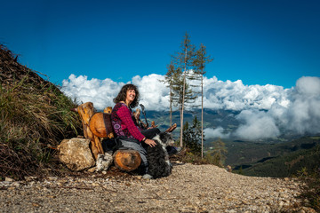 Woman and dog sitting on a bench resting while hiking to the Tschaffonhuette on a high mountain with white clouds above a valley in the background