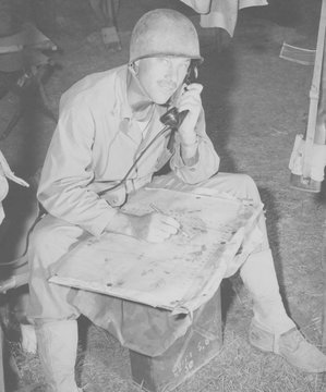 Lt. Col. Raymond Murray taking a message over field phone and plotting positions on a map, August 23, 1950