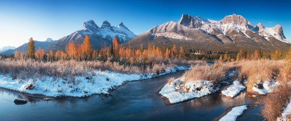 Poster Salmon Sunrise of the Three Sisters and the Bow River from Canmore near Banff National Park. First snow in Canadian Rockies. Beautiful landscape background concept. Christmas time