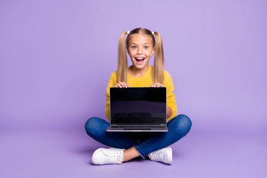 Full size photo of amazed excited child show laptop show touch screen scream wow omg sit crossed folded legs wear casual style outfit isolated over violet color background