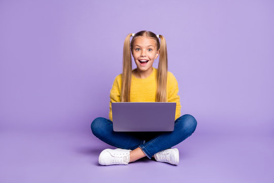 Full size photo of amazed child sit folded crossed legs work computer get social media notification scream wow omg wear yellow pullover sneakers isolated over purple color background