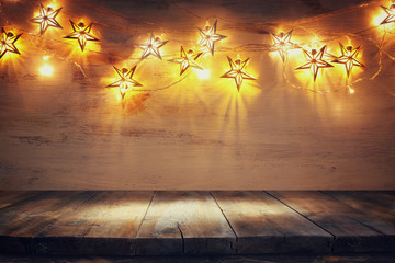 background image of wooden board table in front of Christmas warm gold garland lights. filtered. selective focus