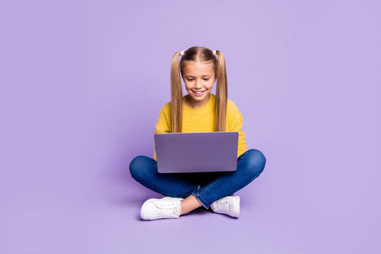 Full length photo of positive interested kid sit legs crossed folded work her laptop read social media news wear casual style clothing isolated over violet color background