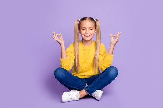 Full length photo of positive cheerful kid sit legs crossed folded train yoga meditate show om sign wear yellow casual style clothing isolated over violet color background