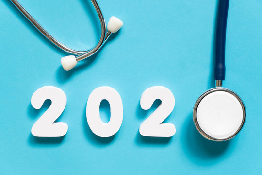 Stethoscope w/ 2020 number on blue background. Happy New Year for health care and medical banner/calendar cover. Creative idea for new trend in medicine treatment and diagnosis concept.