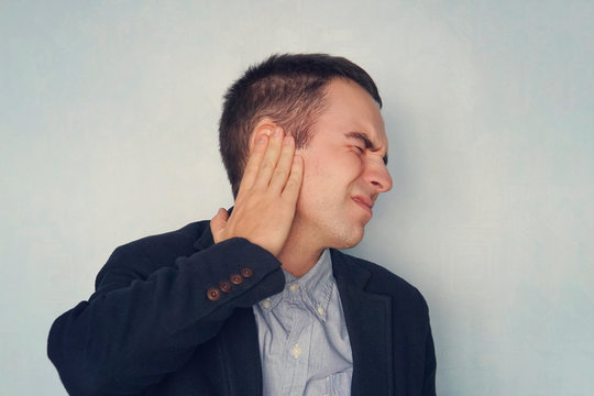 Medical concept. Diseases of the ear. Inflammation in the ear. Young man suffering from Pain in right ear, over blue background