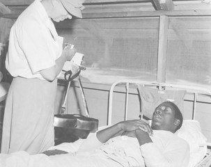 First Lady Eleanor Roosevelt visits a African American soldier in a South Pacific military hospital