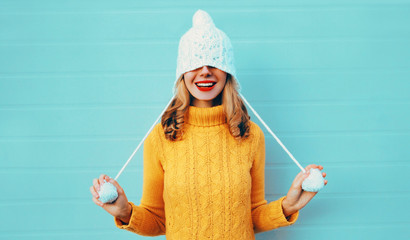 Winter portrait happy smiling young woman having fun pulls a hat over her eyes wearing yellow knitted sweater and white hat with pom pom on blue wall background Wall mural
