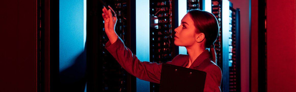 panoramic shot of businesswoman holding clipboard and looking at server room