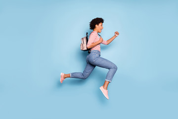Full body profile side photo of positive cheerful afro american girl jump run fast summer school sales hold bag wear striped shirt denim jeans isolated over blue color background