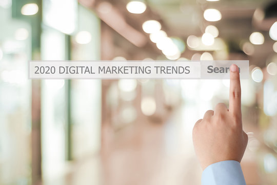 Man hand touching 2020 digital marketing trend, business strategy, on search bar over blur office background, success in business concept