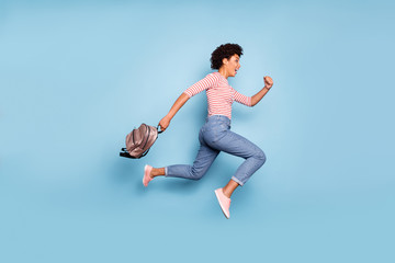 Full length profile side photo of cheerful funny afro american girl jump run summer school discounts hold bag wear striped shirt denim jeans sneakers isolated blue color background