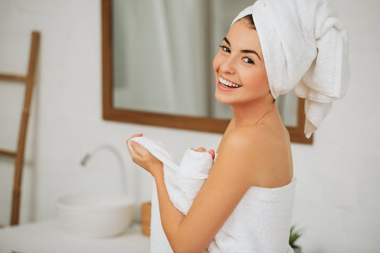 pretty young woman wraps her body in white towel in bathroom