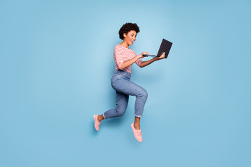 Full length body size side profile photo of pretty cheerful cute nice charming youngster typing before laptop wearing jeans denim striped shirt isolated pastel color blue background Wall mural