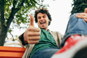 Bottom view of happy smiling man with curly hair, posing for social advertisement with thumb up sitting on the bench outdoors in the city street. Excited cheerful student male making good gesture.